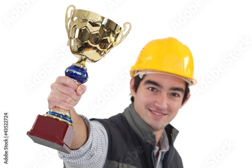 Young tradesman holding up a trophy