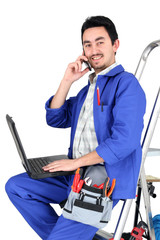 Plumber sat on step ladder holding mobile telephone