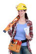 Female construction worker holding tools and a rolled-up plan