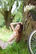 Woman sitting against tree