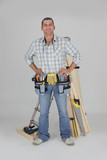 portrait of carpenter fully equipped standing with arms akimbo