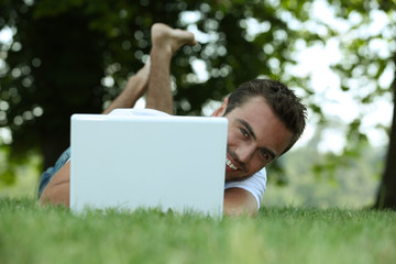 Man using his laptop on a lawn