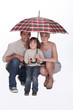 Young family crouching under an umbrella