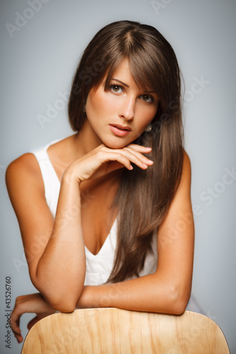 Sensual female in beige dress leaning on her elbows