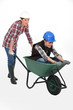 two craftswomen having fun with a wheelbarrow
