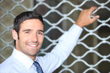 Smiling man standing in front of a shop grille