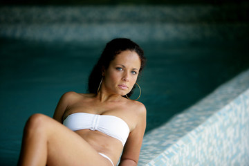 Brunette laying poolside