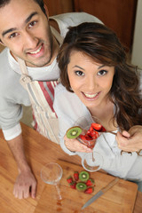 Couple in kitchen with strawberries and kiwi
