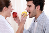 cute young couple eating apples