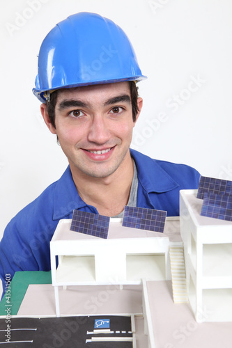 Tradesman posing with an eco-friendly building model