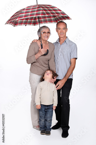 Grandparents and child with an umbrella
