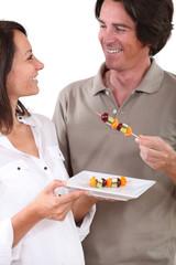 Couple eating fruit skewers