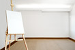 Empty white room with carpeted floor and an empty canvas on an e