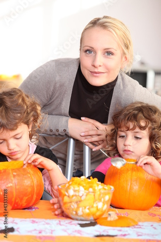 Woman helping her children carve pumpkins