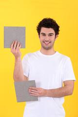craftsman holding two bathroom tiles