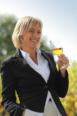 Woman drinking a glass of white wine in a vineyard