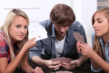 Three teenagers playing cards.