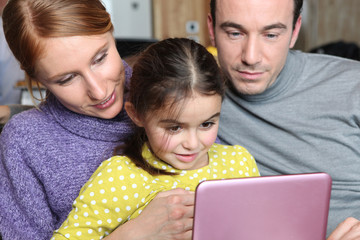 Parents and daughter sat with laptop
