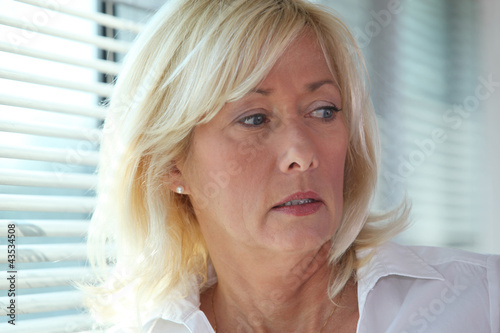 Senior businesswoman stood by window blinds