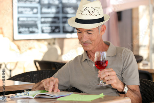 senior on vacation drinking fresh wine in a restaurant