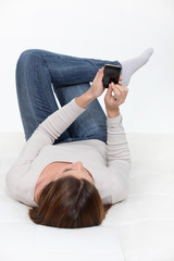 Woman on her phone laying on the floor.
