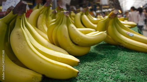 Bunches of bananas for sale in a busy market.