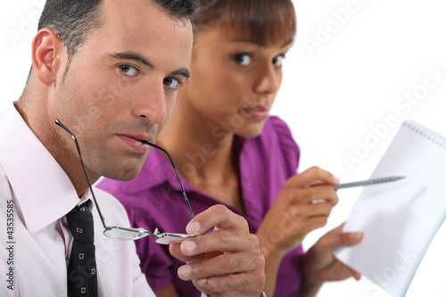 Business couple writing in a pad