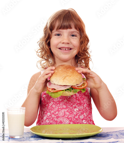 happy little girl with big sandwich