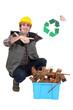 Tradesman kneeling next to a bin and holding up symbol