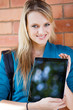 pretty female college student presenting tablet computer
