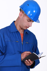 Tradesman writing in his agenda