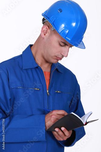 Tradesman writing in his agenda