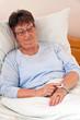 Seniorin mit Ruf Hile Notfall Telefon im Bett