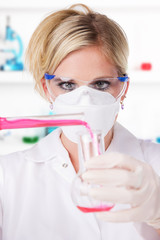 Young attractive laboratory assistant pouring chemical liquid