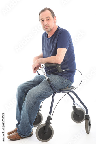Depressed man sitting on medical walker