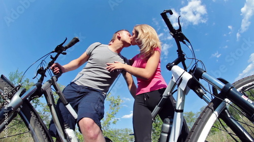 Two attractive couple holding their bikes and kissing