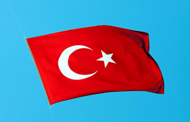 Waving flag of Turkey under sunny blue sky