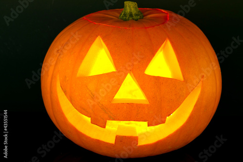 Halloween pumpkin with scary face over black