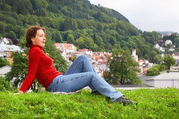 Woman lies on grass at background of Bergen town