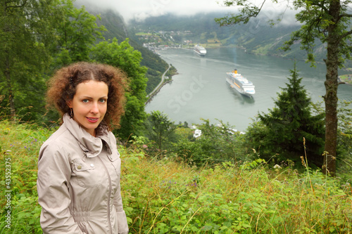 Woman tourist at background of two passenger liners in fiord