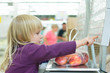 Adorable girl weighting fruits in supermarket