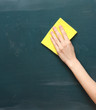 hand with a yellow sponge cleaning the chalkboard
