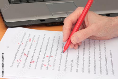 Leinwandbild Motiv Hand Proofreading a Manuscript beside Laptop