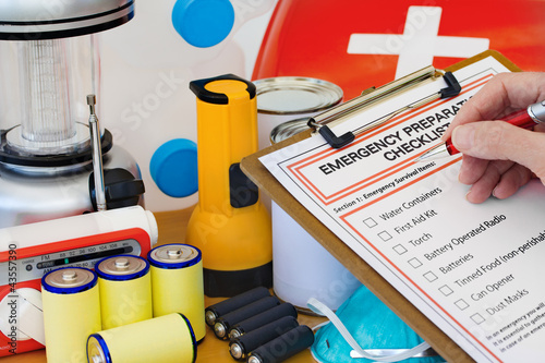 Hand completing Emergency Preparation List by Equipment