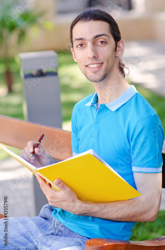 Student outside preparing for exams