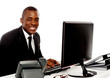 Smiling young corporate man using computer