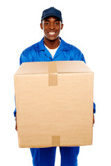 Delivery guy holding big parcel and smiling
