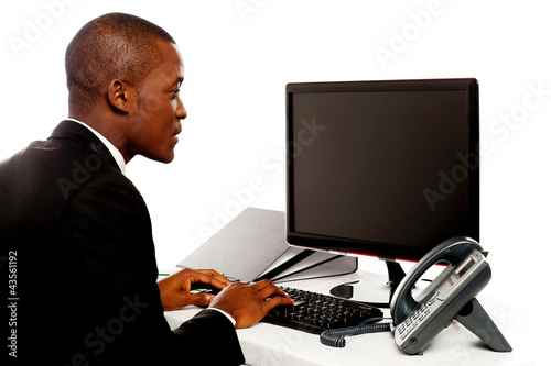 Male executive typing and looking at lcd screen