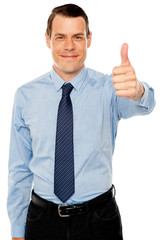Smiling young man with thumbs up gesture
