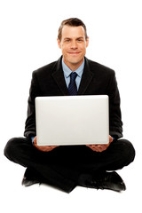 Male executive with laptop sitting on the floor